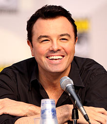A man with short  black hair and a black shirt in front of a microphone. His arms are crossed, and he is laughing.