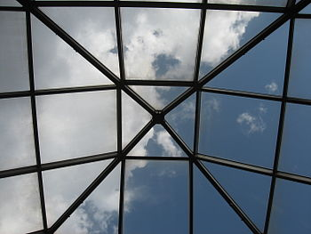 Blue sky and clouds through a large skylight w...