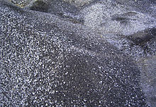 A photograph of dark gray/silver piles of spent shale lumps.