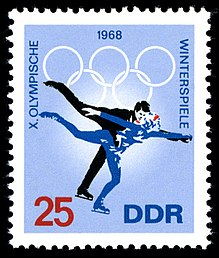 A postage stamp with a blue background and two figure skaters skating, the date 1968 is centered on the top of the stamp along with the Olympic rings. The word «Winterspiele» is written down the right side, the words «X Olympische» are written down the left side. The number 25 is in the lower left corner and the letters «DDR» are in the lower right corner