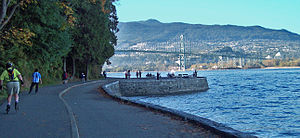 Seawall (Vancouver) - Park visitors walk, bike, roll, and fish on the seawall. The Lions Gate Bridge is in the background.