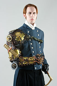 G. D. Falksen in steampunk attire, including a mechanical arm wearable sculpture by Thomas Willeford, utilizing a complex clockwork series of gears