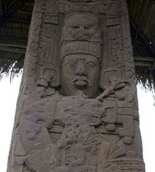 Close up of upper portion of an intricately carved stela, showing the face of a king with elaborate headdress and jewellery