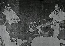 Four men seated around a small, round table