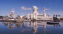Vue de la mosquée Omar Ali Saifuddin depuis le lac. Un navire de cérémonie est accosté près de l'édifice.