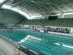 vue d'une piscine, avec dans le fond des tribunes, vides.