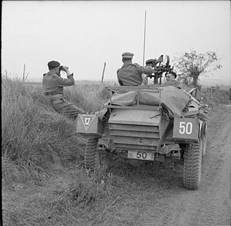 79th Armoured Division (United Kingdom) - Brigadier N. W. Duncan of the 30th Armoured Brigade watches the attack on Caen from beside his Humber scout car outside Beuville, 8 July 1944.