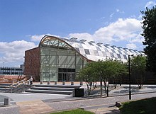 A modern, glass and steel building with a curved roof and steps leading up to it
