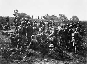 Battle of St Quentin Canal - Men of the American 30th Infantry Division at rest with German prisoners following the capture of Bellicourt, 29 September 1918. In the background are British Mark V Tanks (with 'cribs' for crossing trenches) of the 8th Battalion, Tank Corps, which was one of four battalions of the 5th Tank Brigade allotted to the 5th Australian Division and American Corps for the operation.