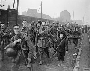 171st (2/1st Liverpool) Brigade - Men of the 8th (Liverpool Irish) Battalion of the King's (Liverpool Regiment) entering Lille, France, 18 October 1918. Note a barefooted French boy with a rifle, clearly given to him by a smiling British soldier on his right.