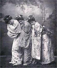 Bond with two women on stage dressed in kimonos, scenery in background.