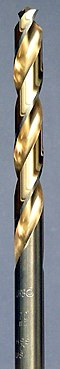 A steel colored twist drill bit with the spiral groove colored in a golden shade.