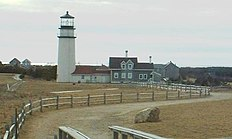 The lighthouse is in the background of the photo, and in the foreground is a large rock, or boulder. In the far distance, on the right, is the Pilgrim Monument tower in Provincetown.