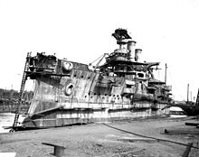 A stern view of an incomplete ship sitting in a drydock with the top of the main turret open, awaiting armor plates.