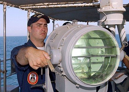 A naval signal lamp, a form of optical communication that uses shutters and is typically employed with Morse code (2002) US Navy 020623-N-5329L-007 Signalman 2nd Class Eric Palmer signals the U.S. Navy mine hunter coastal ship USS Raven (MHC 61.jpg