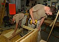 US Navy 040217-N-3994W-010 Builder 3rd Class Zack Mulally, right, builds a child's desk while Engineering Aide 2nd Class Mark Mulhern sands down a bench.jpg