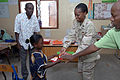 US Navy 071215-N-3931M-096 Chief Information Systems Technician Sheria Sanchious from Combined Joint Task Force-Horn of Africa (CJTF-HOA) presents a gift to a local student at a school dedication ceremony in Ali Adde.jpg