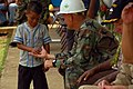 US Navy 080901-N-7498L-218 Chief Equipment Operator James Brock offers a piece of candy to a local child at the Messa Elementary School.jpg