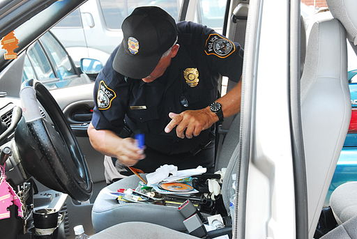 US Navy 090603-N-8732C-078 A Naval Support Activity Washington police officer checks the passenger compartment of a vehicle after the driver was stopped, detained and evaluated for driving under the influence