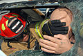 US Navy 091204-N-3289C-121 A firefighter from the Naval Station Rota Fire Department covers the eyes of a training manikin inside a van as the front window is removed during an extrication training exercise.jpg