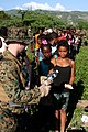 US Navy 100121-M-4988C-007 A Marine hands a bottle of water to a Haitian girl during a relief supply distribution.jpg