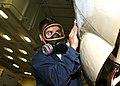 US Navy 100317-N-5049H-016 Aviation Electronics Technician 2nd Class Samuel Hinderliter sands a C-2 Greyhound's fuselage.jpg