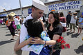 US Navy 100512-N-8335D-302 Electronics Technician 1st Class David Kelley, assigned to the mine countermeasures ship USS Patriot (MCM 7), hugs his wife and child after Patriot arrived in Sasebo, Japan.jpg