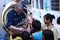 US Navy 101204-N-1375V-193 Musician 3rd Class Zachary Buckwash shows a sousaphone to children at the Goodwill School in Sihanoukville, Cambodia.jpg