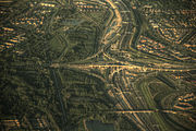 Aerial view of a traffic interchange with trees and houses in the rest of the image