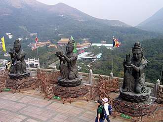 """Tian Tan Buddha - """"The Offering of the Six Devas"""": Buddhistic statues praising and making offerings to the Tian Tan Buddha. Po Lin Monastery can be seen in the background."""