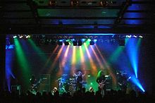 Members of a band, long-haired and dressed in black, perform under multi-colored lights.