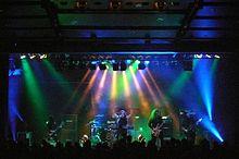 Члены группы, длинноволосые и одетые в черное, выступать под разноцветными огнями.