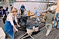 Visitors holding capstan bars turn the capstan.jpg