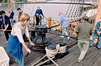 Capstan (nautical) - Modern tourists turn a capstan. Sailors would coordinate the rhythm of their movements by singing a particular type of sea shanty as they walked around the capstan. The tensioned portion of the rope would hoist a foresail and could also be used to lift a heavy spar into position on the mast or to transfer cargo to or from a dock or lighter.