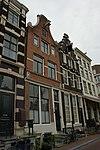 foto van Hoekhuis, gepleisterde voorgevel onder rechte lijst met consoles en houten opzetstukje