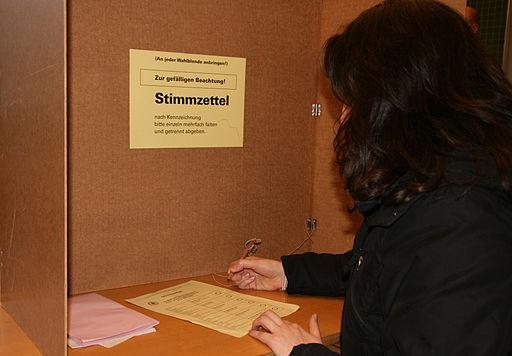 Wählerin in einer Wahlkabine - (C) Alexander Hauk / www.alexander-hauk.de - BILD-BY via Wikimedia Commons