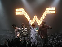"Four men stand in front of an audience; two of them raise their arms. Behind them is an illuminated sign in the shape of the letter ""W""."