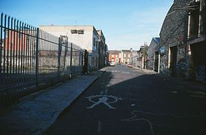 "Windmill Lane Studios - Windmill Lane in Dublin in September 1994. The studios are on the left. On the near left, a fan has written out in blue on the pavement the lyrics to the U2 song ""One""."