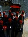 Wine bottles with wax capsules and hot wax pot.jpg
