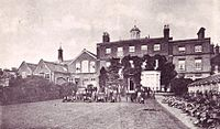 A sepia photograph of the back of a Georgian house and schoolrooms. Edwardian schoolboys and their masters can be seen on the grass in front.