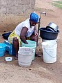 Woman washing clothes and cooking utensils.jpg