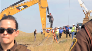 Color image of Lakota man locked down to construction equipment at direct action against Dakota Access Pipeline