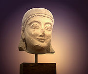 Head of a kouros in the Athens National Archaeological Museum bearing a typical archaic smile.