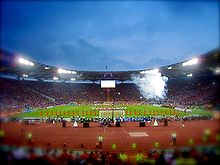 A panoramic view of a stadium. Several people are on the pitch.
