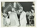 A bride and groom with confetti on their heads standing outside a church on wedding day (AM 88048-2).jpg