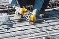 A worker ties together reinforcing bar, or rebar, to strengthen concrete floors for a facility that will house 372 students as part of the Herat University Women's Dormitory Project in Herat province 140311-A-DT641-242.jpg
