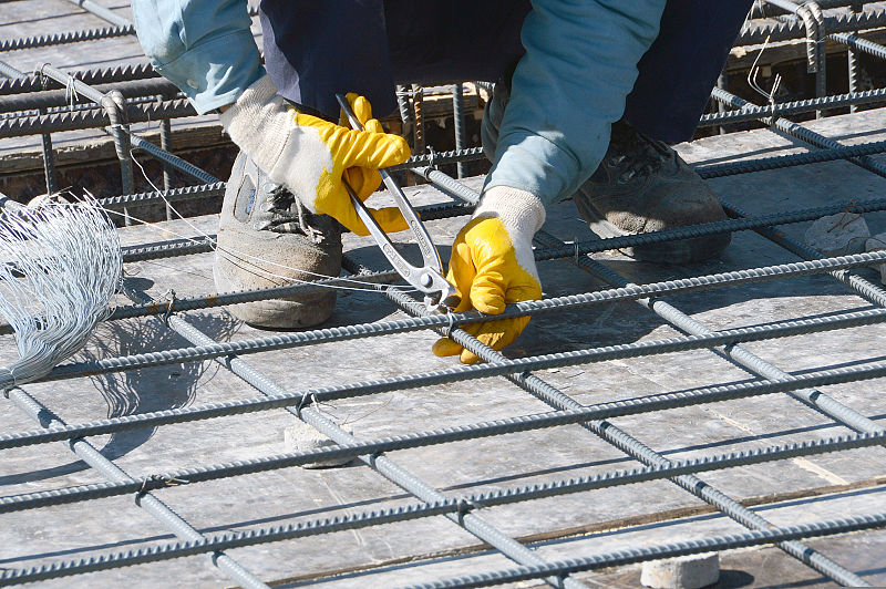filea worker ties together reinforcing bar or rebar to strengthen concrete floors for a facility that will house 372 students as part of the herat