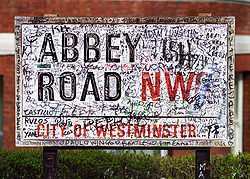 An Abbey Road street sign, complete with Beatles-related graffiti