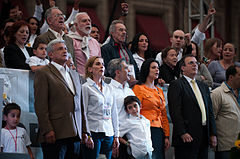 Mancera, in the center of the image, is being accompanied by a group of people that is standing in front of a crowd.