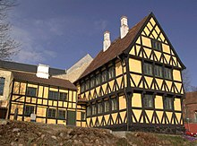 Large three-storied, half-timbered house, with plaster filling.